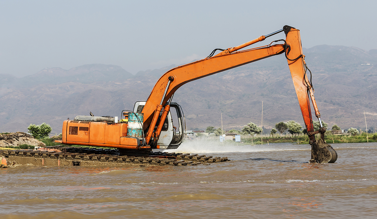 excavator removing dredging sediments
